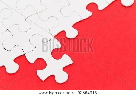 Incomplete white puzzle with red color background