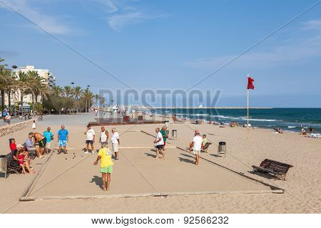 Seniors Spaniards Play Bocce On Sandy Beach