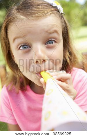 Head And Shoulders Portrait Of Girl Blowing Party Hooter