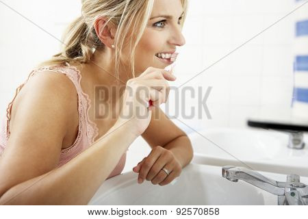 Woman In Bathroom Brushing Teeth
