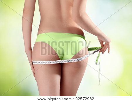 Bum and legs of slim woman over green background with meter