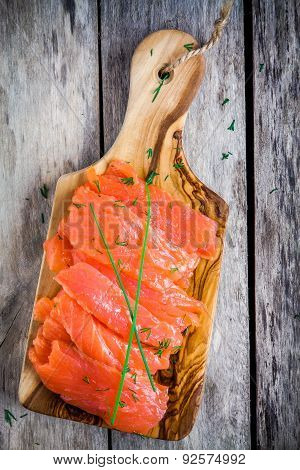 Slices Of Smoked Salmon On A Wooden Chopping Board With Green Onion