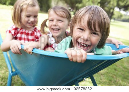 Three Children Sitting In Wheelbarrow