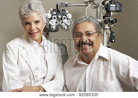 Portrait Of Female Optician With Patient In Surgery