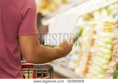 Close Up Of Man Reading Shopping List In Supermarket