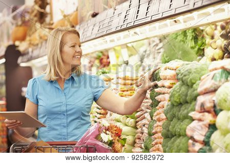 Woman Reading Shopping List From Digital Tablet In Supermarket