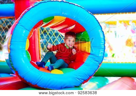 Cute Happy Kid, Boy Playing In Inflatable Attraction On Playground
