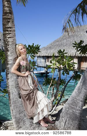 The beautiful woman with a rose at a palm tree. Bora-bora Tahiti