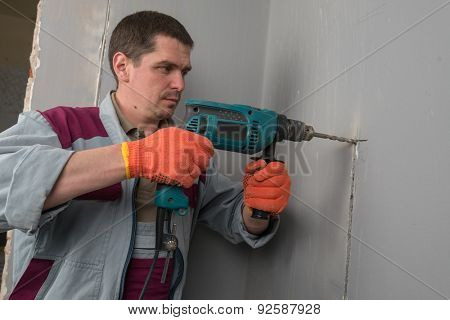worker drills a wall in house