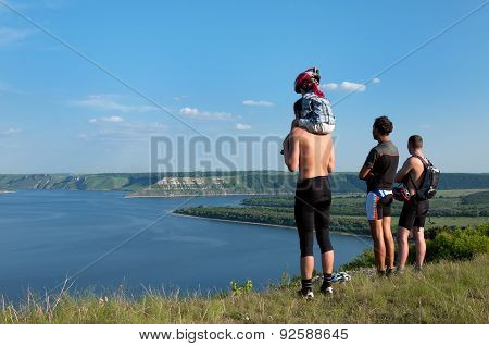 Three Tourists With  Small Child Standing On Shore Beautiful Reservoir