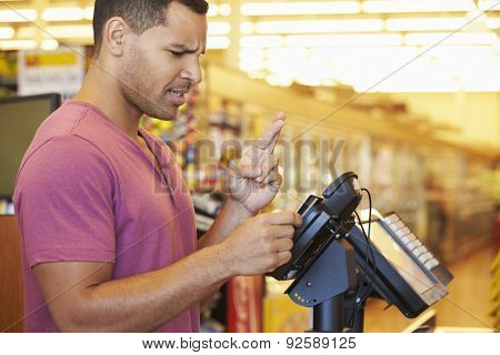 Hopeful Customer Paying For Shopping At Checkout With Card Crossing Fingers