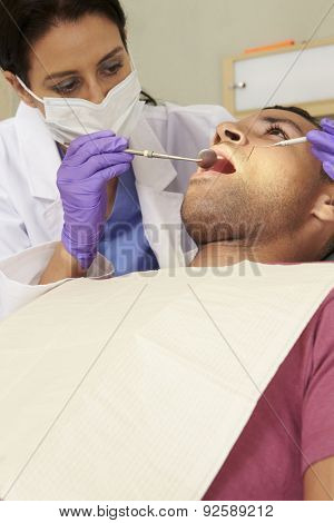 Man Having Check Up At Dentists Surgery
