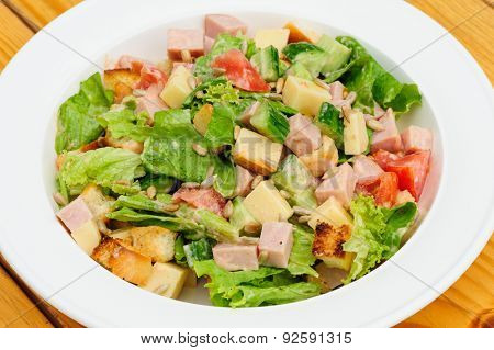 Appetizer salad with cheese, ham, fresh tomatoes, lettuce, sunflower seeds and crackers