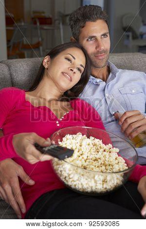 Hispanic Couple On Sofa Watching TV And Eating Popcorn