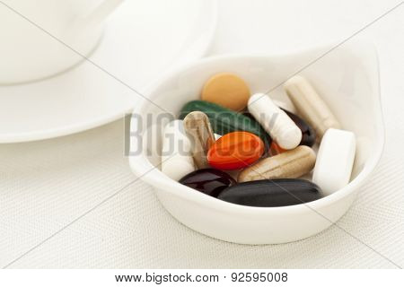 bowl of vitamin, supplement  and medicine pills - breakfast concept - shallow depth of field