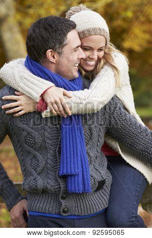 Romantic Couple Sitting On Fence In Autumn Woodland