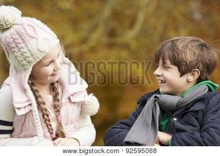 Two Children Leaning Over Wooden Fence Talking