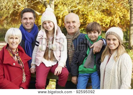 Multl Generation Family By Wooden Fence On Autumn Walk