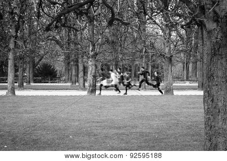 Black And White Image Of A Group Of Children Running In A Park