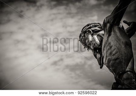 Crucified Jesus Christ against the cloudy sky