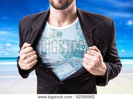 Businessman stretching suit with Brazilian money on beach background