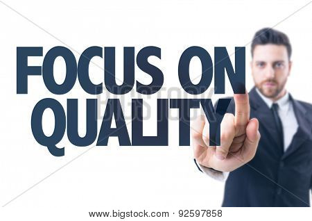 Business man pointing the text: Focus On Quality