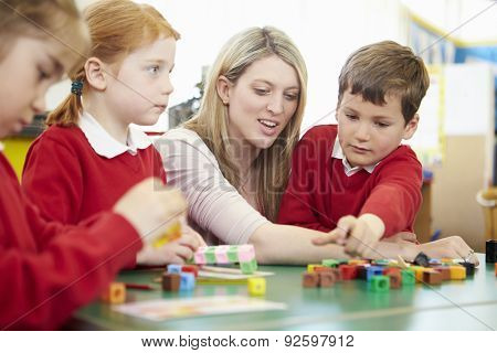 Pupils And Teacher Working With Coloured Blocks