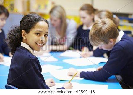 Portrait Of Pupil In Classroom With Teacher