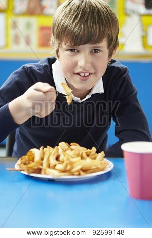 Male Pupil Eating Unhealthy School Lunch