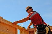 foto of rafters  - Building contractor worker measuring out the top plate of the wall in preparation for the rafter on the second floor on a new home construciton project - JPG