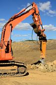 stock photo of excavator  - A large hydralic rock breaker ram hammer installed on a track hoe excavator being used to break up stones at a new commercial construction development project - JPG