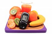 stock photo of immune  - Glucose meter fresh ripe natural fruits and glass of juice on cutting board concept for diabetes healthy nutrition and strengthening immunity - JPG