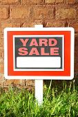 image of yard sale  - Wooden Yard Sale sign in green grass on red brick wall background - JPG
