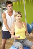 picture of encouraging  - Woman Exercising Being Encouraged By Personal Trainer In Gym - JPG
