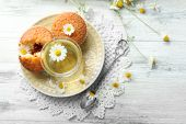 stock photo of chamomile  - Glass of chamomile tea with chamomile flowers and tasty muffins on color wooden background - JPG