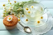 picture of chamomile  - Cup of chamomile tea with chamomile flowers and tasty muffin on color wooden background - JPG