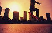 stock photo of skateboard  - closeup of skateboarder skateboarding at sunrise city - JPG
