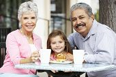 image of grandparent child  - Grandparents With Granddaughter Enjoying Snack At Outdoor Caf - JPG