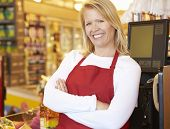 picture of cashiers  - Female Cashier At Supermarket Checkout - JPG