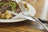 picture of flank steak  - Sliced juicy skirt steak with potatoes and arugula garnish - JPG