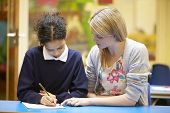 stock photo of 11 year old  - Teacher With Female Pupil Reading At Desk In Classroom - JPG