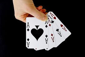 stock photo of spade  - croupier player holding in hand card ace of spades four of a kind on black background - JPG