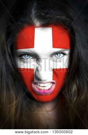 Portrait of a woman with the flag of the Switzerland painted on her face.
