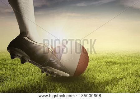Foot of football player kicking a ball with flag of France on the green grass