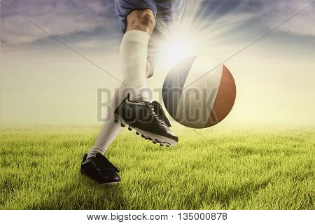 Image of foot of football player doing exercise by kicking a soccer ball at the field