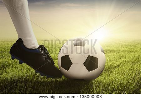 Close up of foot of soccer player wearing football shoe and and kicking a soccer ball on the meadow