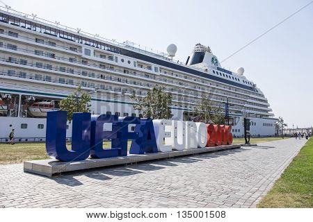 BORDEAUX FRANCE - 16 JULY 2015 - The magnificent Crystal Serenity cruise ship is docked on the river Gironde in the heart of Bordeaux behind the large colorful sign for UEFA EURO 2016.