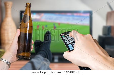 Man is relaxing with legs on table and is watching football match on tv and holds remote controller and beer.