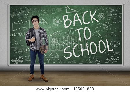 Picture of a male high school student carrying backpack and standing in the class with text of Back to School on the chalkboard