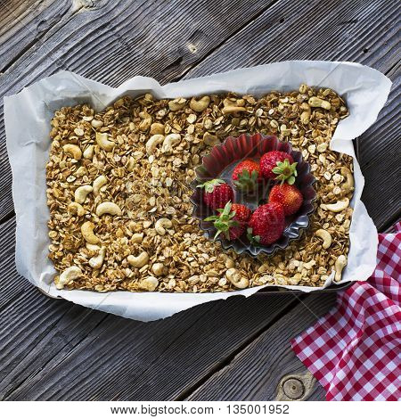 Healthy breakfast dessert. Crunchy granola with homemade pecan nuts served with fresh strawberries, milk, yogurt, liquid honey and fresh oregano. On a dark wooden background